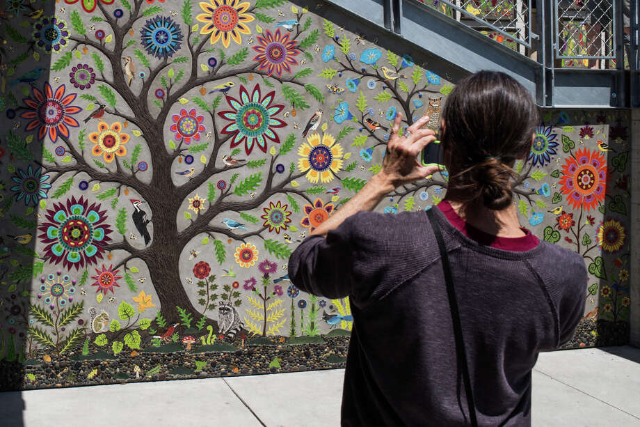 A tourist takes a photo of a mural next to the grand staircase during Pike Place Marketfront's grand opening on Thursday, June 29, 2017. Photo: GRANT HINDSLEY, SEATTLEPI.COM / SEATTLEPI.COM