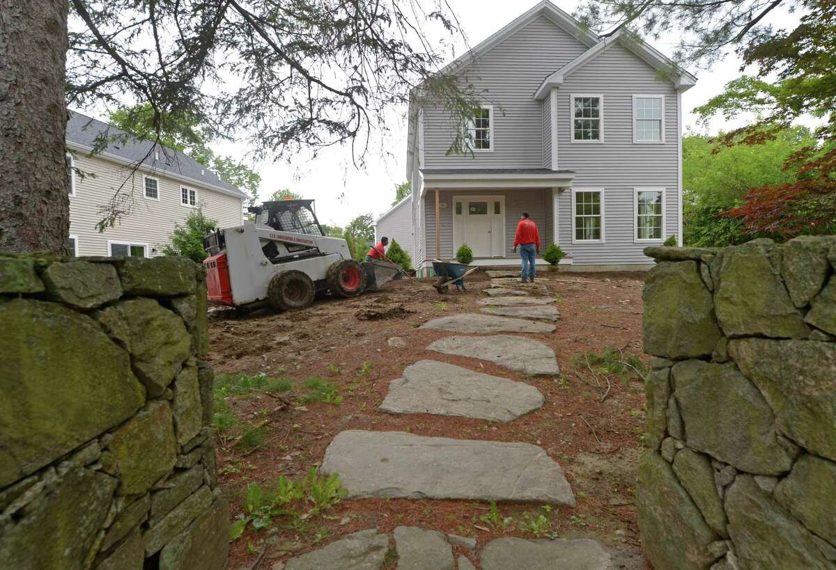 Workers with CFC landscaping plant shrubs as the construction of three new homes where one historic home once stood is nearly completed Tuesda at 319 Flax Hill Road in Norwalk.