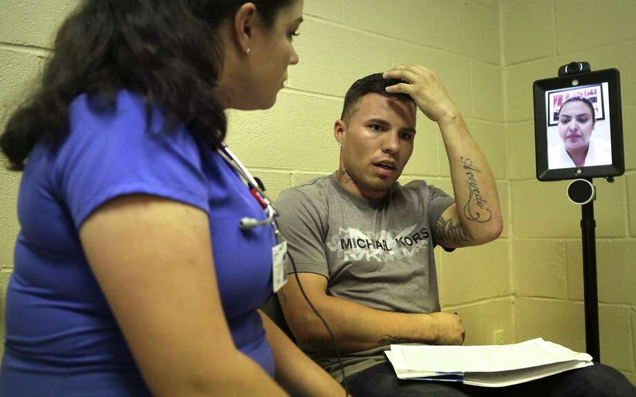 Abraham Gomez, center, tells student nurse Stephenie Decker, left, about an injury to his head that has caused him to have frequent headaches, at a health clinic in the El Cenizo Community Center in El Cenizo, Tx, on Tuesday, June 27, 2017. The U.S. Army and students from the Texas A&M medical system have been working together on a large-scale health care training exercise in small communities around Laredo, TX. At left is an off-site interpreter to help with translations. Photo: Bob Owen, Staff / San Antonio Express-News / ©2017 San Antonio Express-News