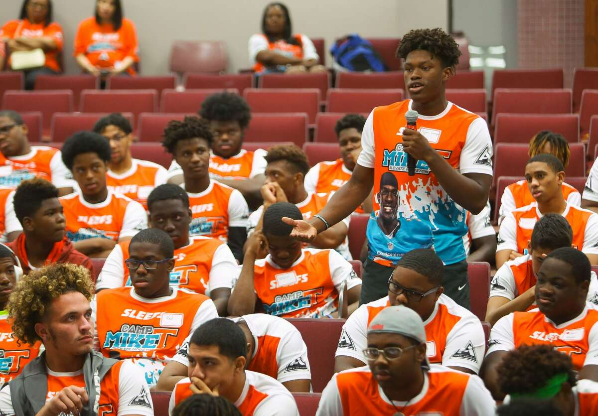 Tylan George, 15, asks Constable Alan Rosen a question about what exactly to do when pulled over by law enforcement during a town hall stye meeting at Miami Dolphins safety Michael Thomas' annual football camp at Aldine's Thorne Stadium, Thursday, June 29, 2017, in Houston.