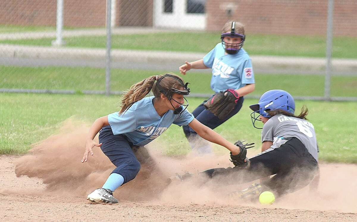 Wilton shortstop Avery Samai, left, can't come up with the ball as Rowayton's Nina Garbarino slides safely into second with a stolen base during Thursday night's District 1 Little League softball pool play finale at McMahon High School. Rowayton defeated Wilton 14-4. Wilton's Katherine Costanzo, rear, looks on.