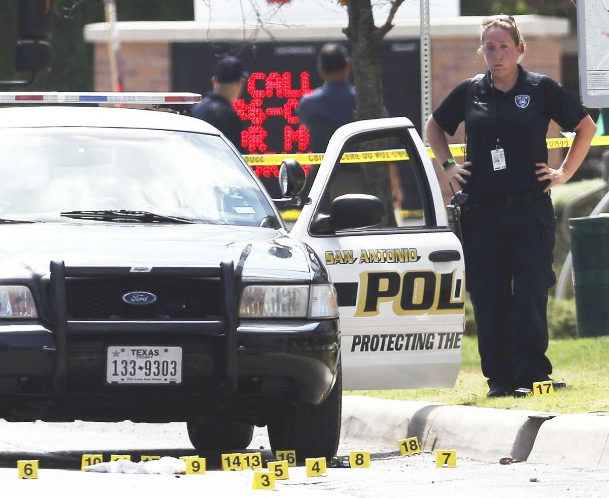 Investigators examine bullet casings on Evergreen Street near Main after police and and an unknown individual exchanged gunfire after an apparent traffic stop. (Kin Man Hui/San Antonio Express-News)
