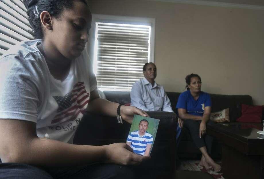 Samrawit Kidanemariam Menghistu, 17, holds a photo of her bother, Aron Kidanemariam Menghistu, 22, who remains in Kenya waiting to immigrate to the United States. Photo: Paul Kuroda / Paul Kuroda / Special To The Chronicle / online_yes