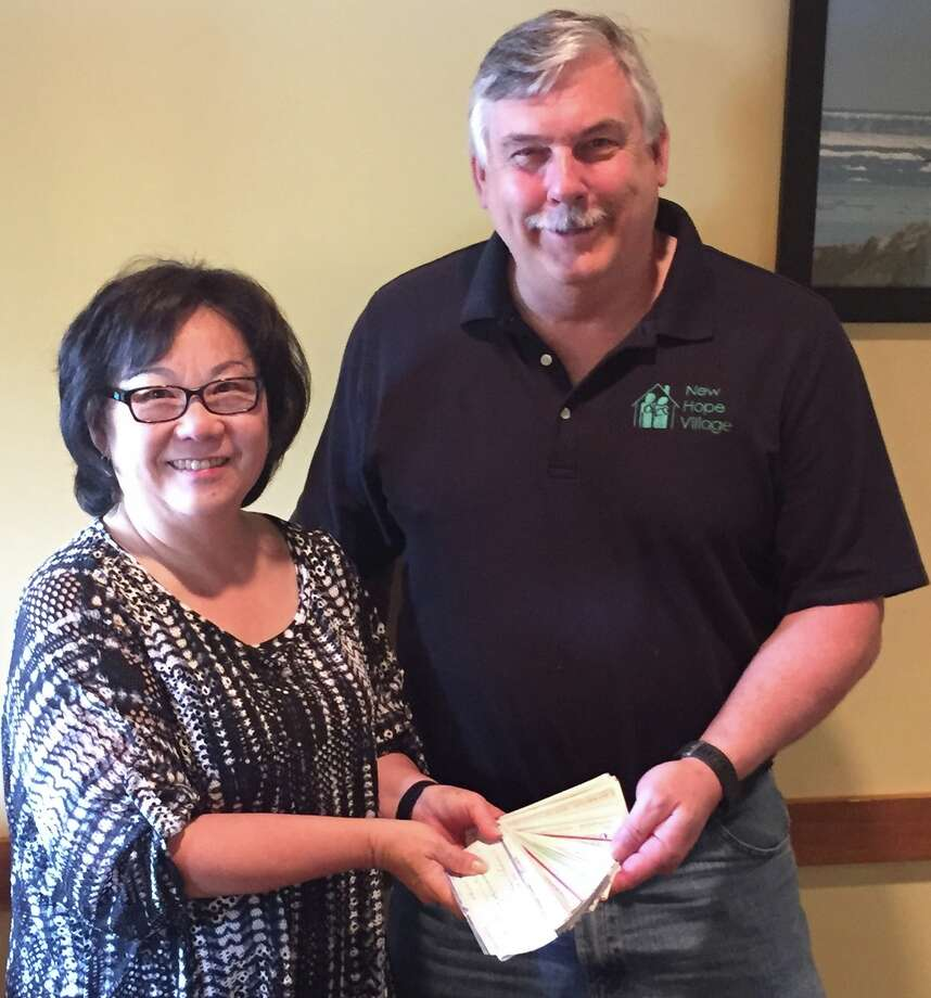 Midland 100 Club Chair Tina Van Dam presents checks from club members to New Hope Village Executive Director John Congleton. (Photo provided)