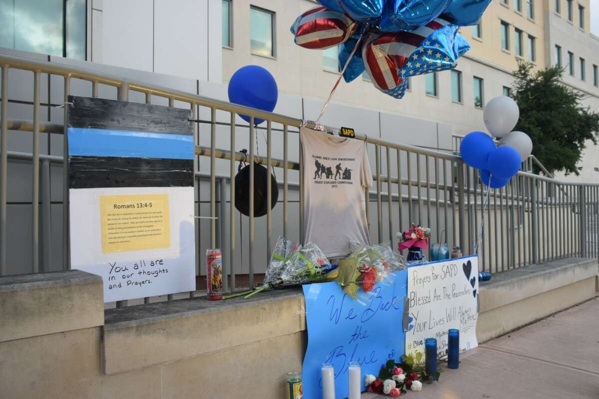 A memorial is building outside Public Safety Headquarters in downtown San Antonio after two officers were shot on Thursday, June 29, 2017, during a crime prevention patrol. The two officers are critically wounded, while one suspect has been killed and another suspect detained.