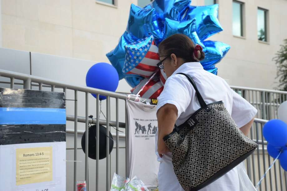 Maria Rubio, an employee at a nearby Bill Miller's BBQ, paused at a memorial for two San Antonio police officers Friday, June 30, 2017. Officer Miguel Moreno, 32, was pronounced dead at 11:11 a.m. Friday at the San Antonio Military Medical Center and Officer Julio Cavazos, 36, who was shot in the chest and is expected to survive Photo: Caleb Downs / San Antonio Express-News