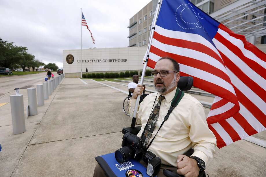 Scott Crawford, with the Mississippi Coalition for Citizens with Disabilities, waves his disability symbol American flag outside the federal courthouse in Jackson, Miss., as he and other Medicaid recipients, social service activists and supporters stage a protest outside the offices of Sen. Roger Wicker, R-Miss., on Thursday. Photo: Rogelio V. Solis, Associated Press