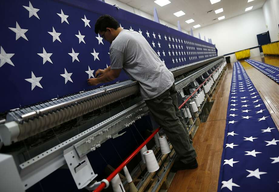 A worker inspects a sheet of stars after embroidery at the FlagSource factory in Batavia, Ill. Photo: Jim Young, Bloomberg