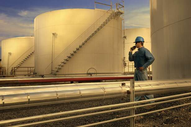 A man stands next to storage tanks at an oil refinery in this Getty stock image.