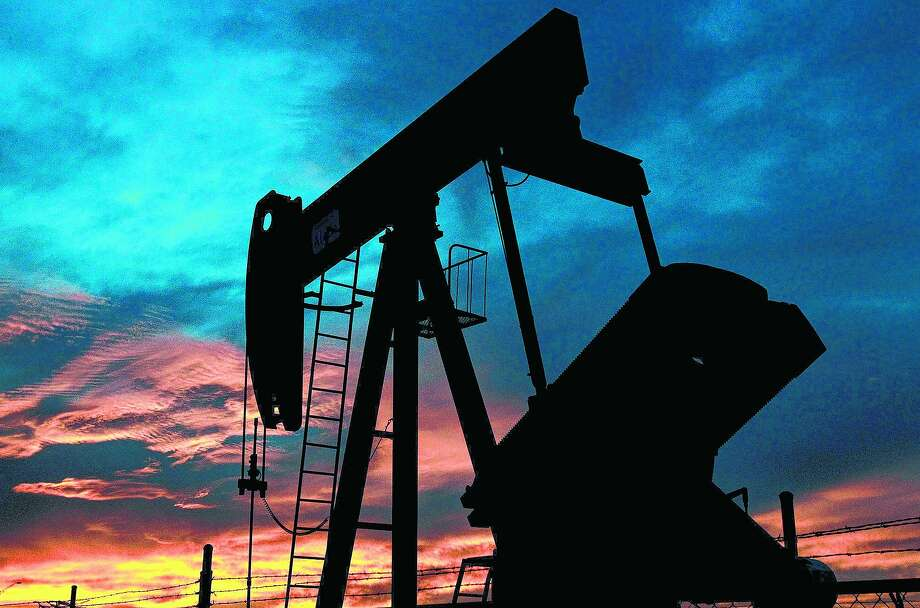 A pumpjack rocks back and forth as the sun sets Wednesday April 2, 2014 in Stanton, Texas. Photo: JOHN DAVENPORT, SAN ANTONIO EXPRESS-NEWS