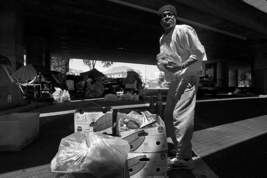 Marcus Emery grabs food after a homeless outreach van delivered the goods at Northgate Avenue and Sycamore Street in Oakland. Photo: Santiago Mejia, The Chronicle