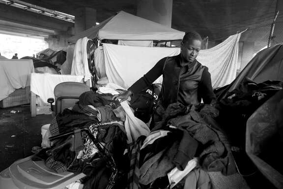Shonee Stringer organizes her belongings in front of her tent in Oakland, Calif. on Friday, June 30, 2017. Stringer has been living at the well-established homeless encampment on Northgate Avenue and 27th Street since January.