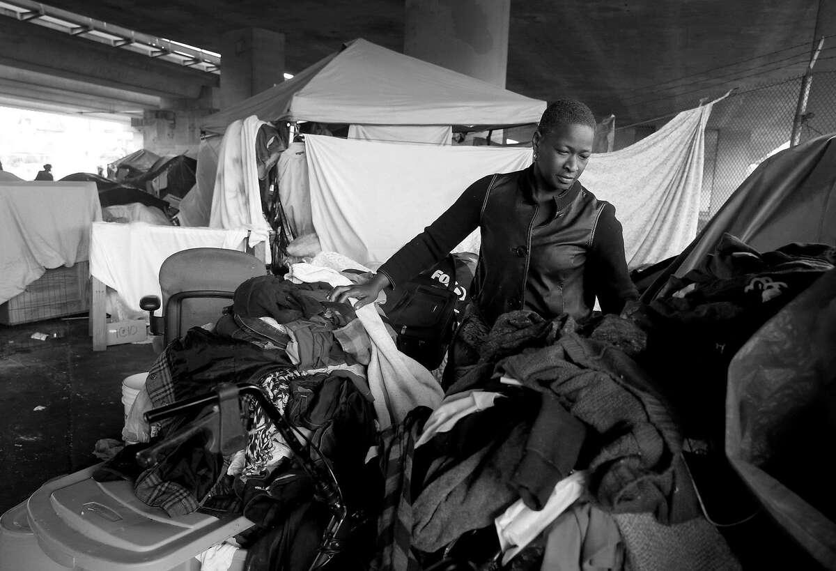 Shonee Stringer organizes her belongings in her tent in Oakland.