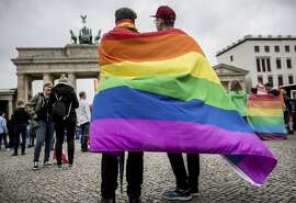 Men with rainbow flags stand in front of the Brandenburg Gate at an event organized by the SPD to celebrate the legalization of same-sex marriage in Berlin, Germany, Friday, June 30, 2017. The German Bundestag has voted to legalize same-sex marriage in the country. (Michael Kappeler/dpa via AP)
