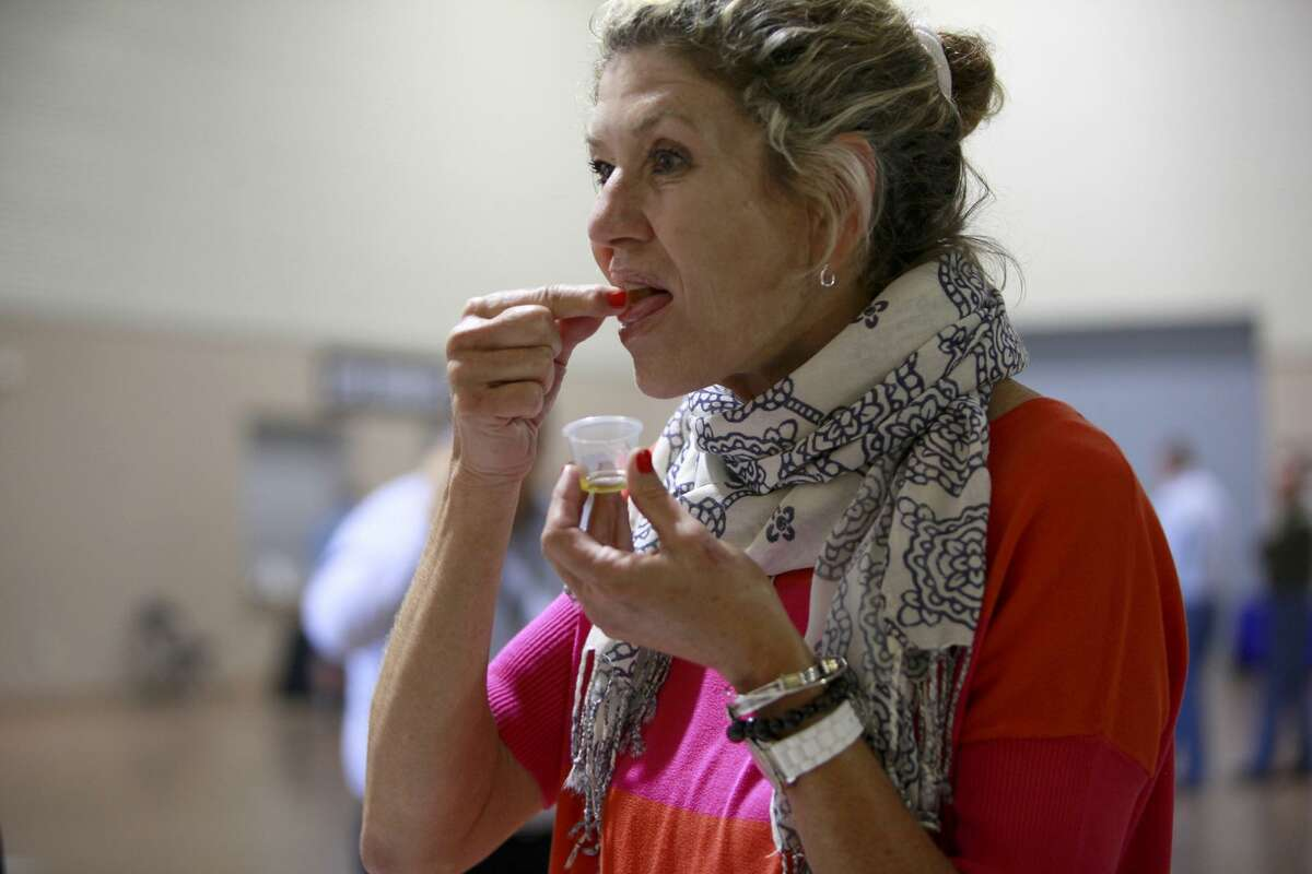 Lisa Mcglone, who owns the Dry Escondido Ranch in Kenedy, TX, tries some croutons with olive oil at the Texas Olive conference at Freeman Coliseum on June 16, San Antonio.