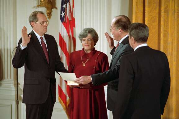 (Original Caption) Washington: Judge Anthony Kennedy is given the constitutional oath, required of all federal employees, by Chief Justice William Rehnquist during a White House ceremony. Kennedy's wife Mary holds a Bible as President Reagan (R) looks on.
