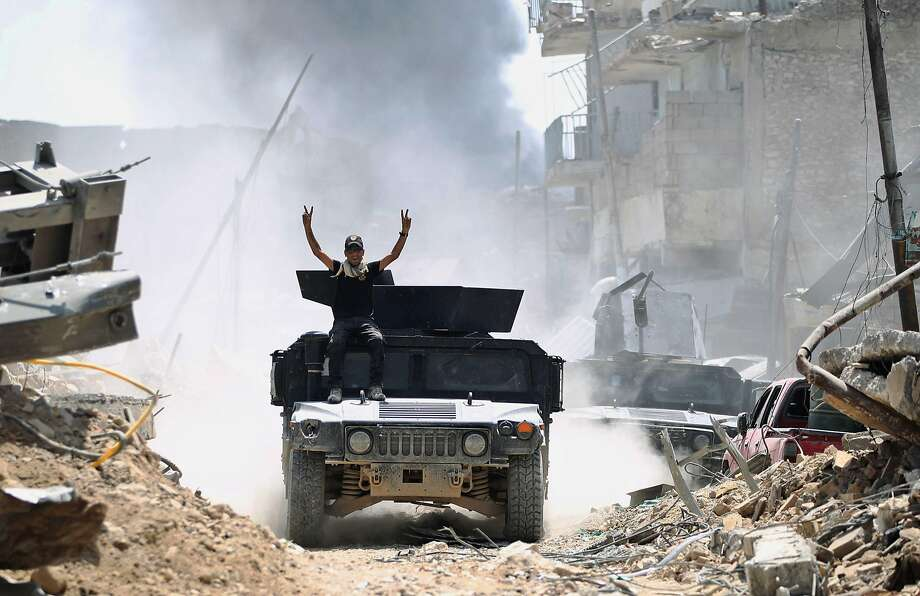 """TOPSHOT - A member of the Counter-Terrorism Service (CTS) seated on the top of an advancing humvee raises the victory gesture while advancing in the Old City of Mosul on June 30, 2017, as Iraqi government forces continue their offensive to retake the city from Islamic State (IS) group jihadists. Iraq will declare victory in the eight-month battle to retake second city Mosul from jihadists in the """"next few days,"""" a senior commander said on June 30, 2017. Iraqi forces launched the gruelling battle for Mosul on October 17, 2016, advancing to the city and retaking its eastern side before setting their sights on the smaller but more densely populated west. / AFP PHOTO / AHMAD AL-RUBAYEAHMAD AL-RUBAYE/AFP/Getty Images Photo: AHMAD AL-RUBAYE, AFP/Getty Images"""