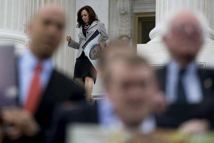 Sen. Kamala Harris, D-Calif., joins fellow Democratic Senators as they hold up signs of constituents who would be adversely affected by the proposed Republican Senate healthcare bill during a news conference outside the Capitol Building in Washington, Tuesday, June 27, 2017. (AP Photo/Andrew Harnik)