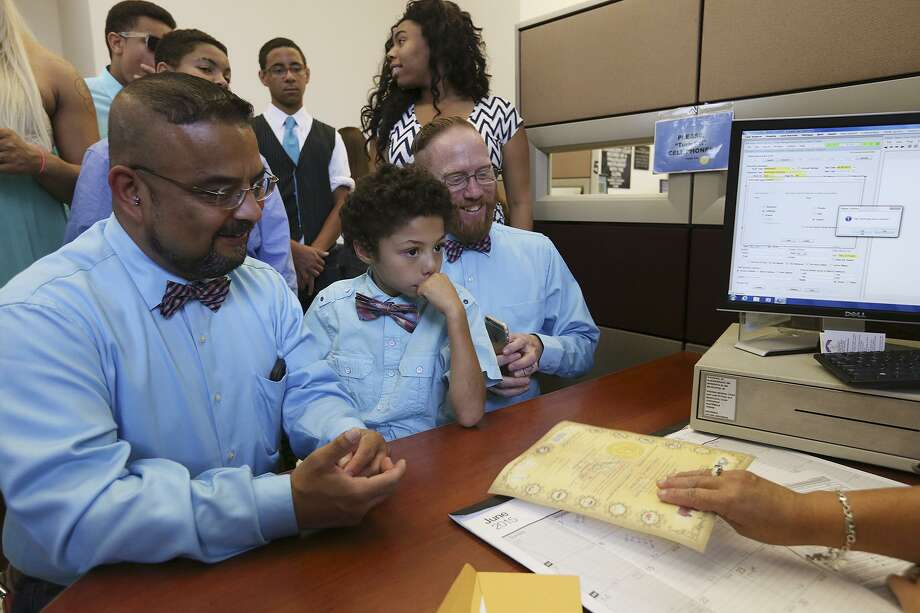 Andres Sutherland-Trevino (center left), 46, and Mark Sutherland-Trevino, 49, obtain their marriage license at the Bexar County Clerk's Office after the U.S. Supreme Court ruled in favor of same-sex marriages in this 2015 photo. In between them is their son, Nathan, 9. The Texas Supreme Court held Friday that same-sex couples are not necessarily entitled to government employment benefits. Photo: San Antonio Express-News File Photo / © 2015 San Antonio Express-News