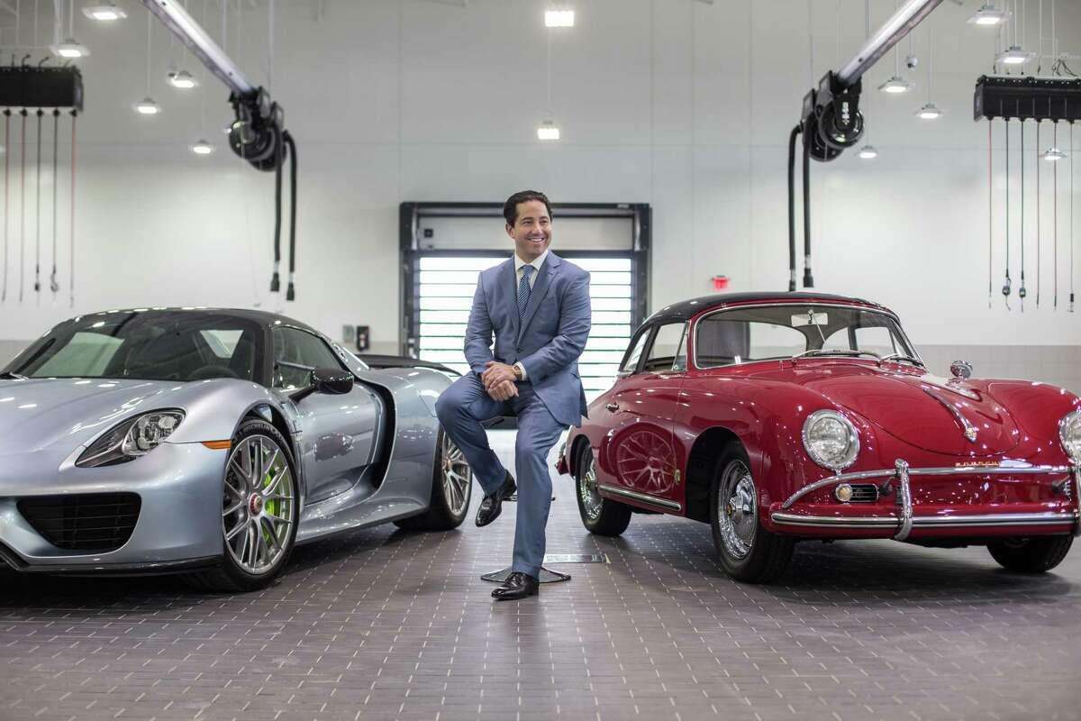 Todd Blue, owner of a new flagship Porsche dealership, poses for a portrait between a Porsche 918 Spyder and a Porsche 1600 in the dealership garage Thursday June 29, 2017. (Michael Starghill, Jr.)