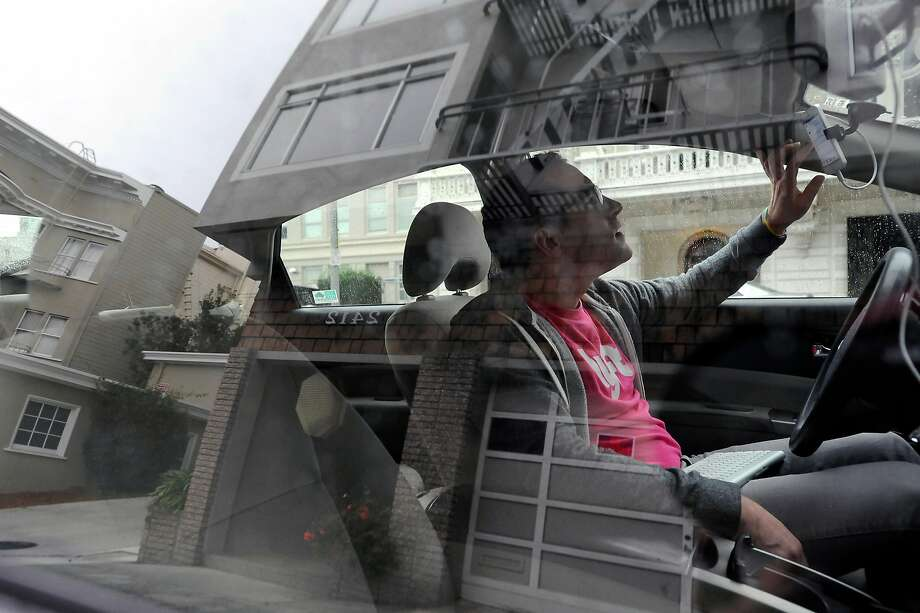 Lyft driver Andrew Kucharski, who is deaf, checks his phone while waiting for customers during a shift in San Francisco in Dec. 2014. Lyft's market share in the city grew from 32 percent to 38 percent from 2016 to 2017. Photo: Michael Short, Special To The Chronicle