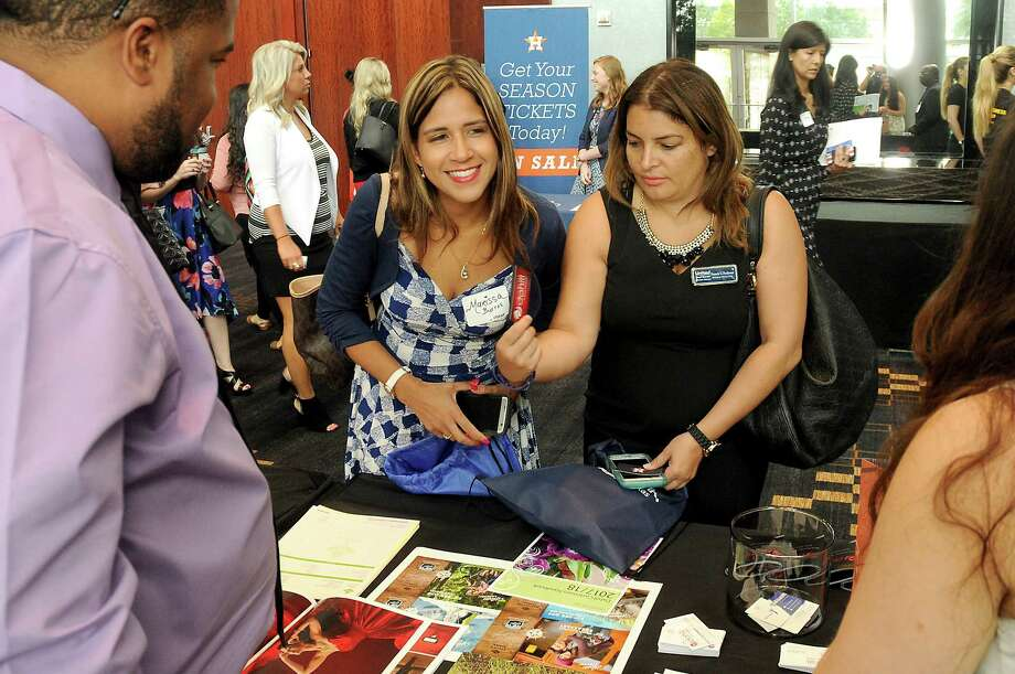 Marissa Burres and Francis Perdomo browse for information Friday at the Hispanic Chamber of Commerce's annual Women's Leadership Conference and Business Expo. Photo: Dave Rossman, Freelance / Dave Rossman