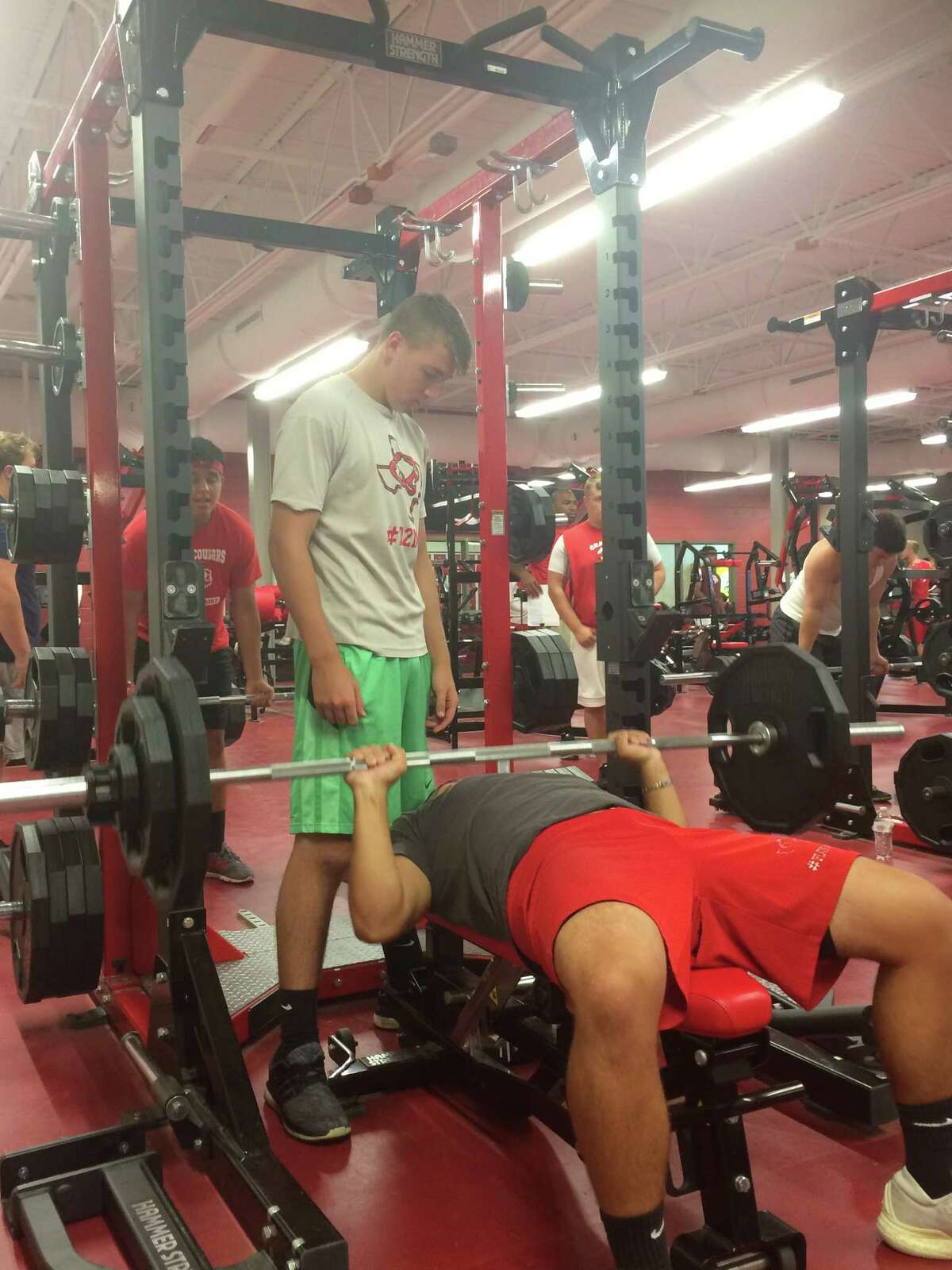 Michael Hernandez does a bench press rep while Weslee Woodard spots and watches at the Crosby football EDGE summer conditioning camp