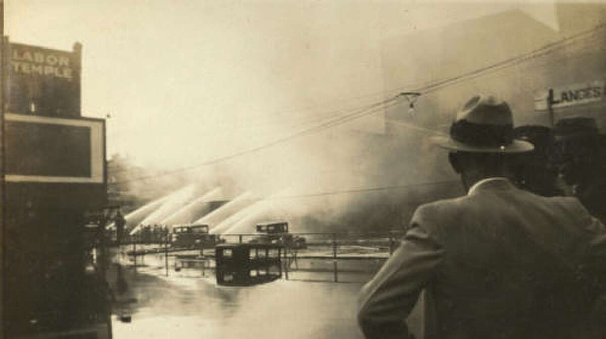 Spectators watch while firefighters spray a building onfire, 1920.