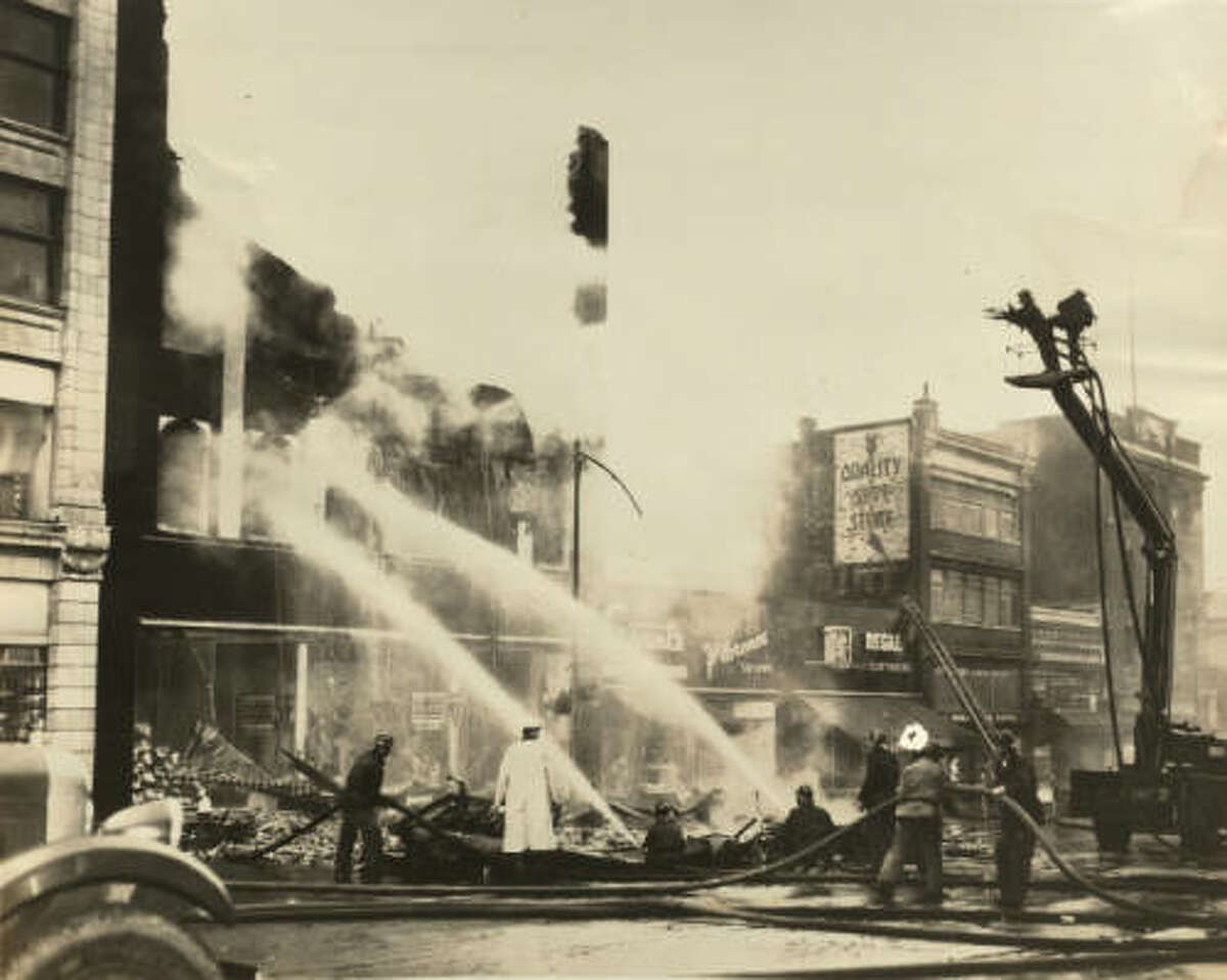 A civilian bucket truck, on the right, was commandeered by the fire department to fight a fire in the mid to late 1930s.