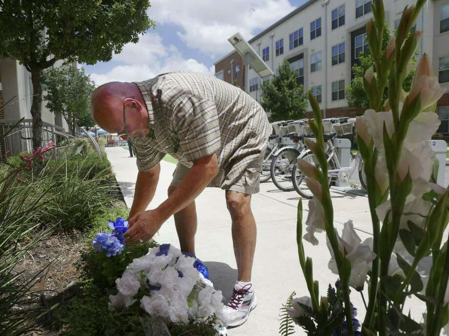 Rocky Jaques places a blue carnation on the site where on Thursday two police officers were shot during a confrontation with two men, one of whom died in the gunfight, near the intersection of Howard and Evergreen on Friday, June 30, 2017. One of the officers, Miguel Moreno, died of a head wound on Friday. Photo: Billy Calzada /San Antonio Express-News / San Antonio Express-News