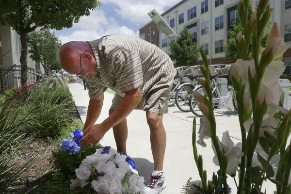 Rocky Jaques places a blue carnation on the site where on Thursday two police officers were shot during a confrontation with two men, one of whom died in the gunfight, near the intersection of Howard and Evergreen on Friday, June 30, 2017. One of the officers, Miguel Moreno, died of a head wound on Friday.