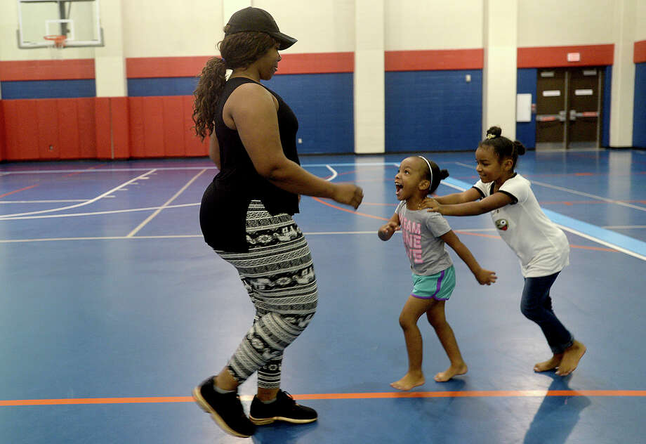 Sisters Jasmine and Zoe Sims chase after their mother Latoya Burkes as she joins in the routine during the Zumba by Jentonic class held Thursday at the Sterling Pruitt Activity Center. Instructor Jennafer Hamilton offers free Zumba classes Tuesday and Thursdays at 6:15, and paid sessions, which are $2 per class, Mondays and Wednesdays at 7:15. Photo taken Thursday, June 29, 2017 Kim Brent/The Enterprise Photo: Kim Brent / BEN