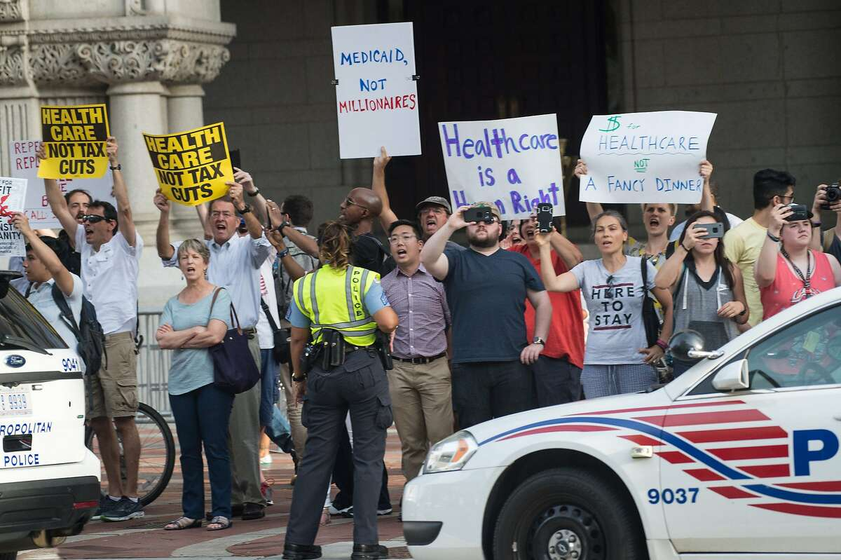 Protesters hold signs as US President Donald Trump arrives at the Trump International hotel in Washington, DC, on June 28, 2017 to attend a fundraiser for his 2020 campaign. / AFP PHOTO / NICHOLAS KAMMNICHOLAS KAMM/AFP/Getty Images