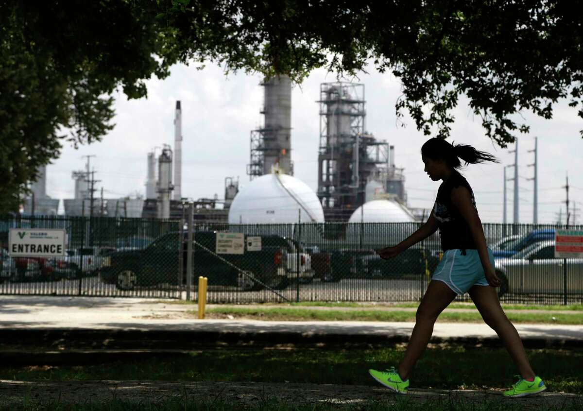 A teenage girl walks around the track of a park across the street from the Valero refinery Monday, Aug. 4, 2014, in the Manchester neighborhood of Houston. (AP Photo/Pat Sullivan)