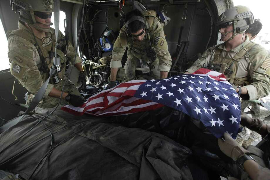 In 2010, Tech. Sgt. Jeff Hedglin (right) drapes an American flag over the remains of one of two U.S. soldiers killed minutes earlier in an IED attack in Afghanistan. July Fourth is a time to remember those who fought for our freedom. Photo: Associated Press File Photo / AP