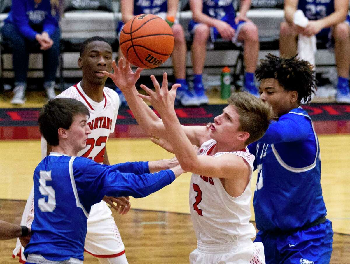 Porter guard Pierce Spencer (2) grabs a rebound past Barbers Hill guard Bryce Harlow (5) during the third quarter of a District 21-5A high school boys basketball game at Porter High School Friday, Feb. 10, 2017, in Porter. Porter defeated Barbers Hill 71-61.