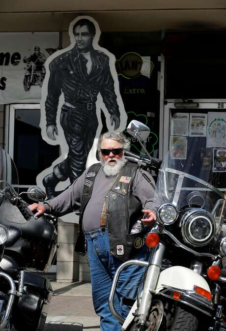 "Motorcycle rider Cal Wilson of Idyllwild, Ca. is know as ""Lone Wolf-No Club"", he is in front of a Marlon Brando poster at Johnny's Bar and Grill, on opening day marking the 70th anniversary of the Hollister Independence Rally on Friday June 30, 2017, in Hollister, Ca. Photo: Michael Macor, The Chronicle"