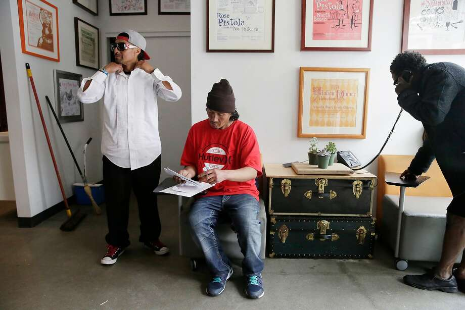 Javier Rodriguez (left) and Eric Delgado, who are homeless, rest at the North Beach Citizens aid center while Dillard Lockhard makes a call. Lockhard says the center helped him with housing and other services while he was homeless . Photo: Lea Suzuki, The Chronicle