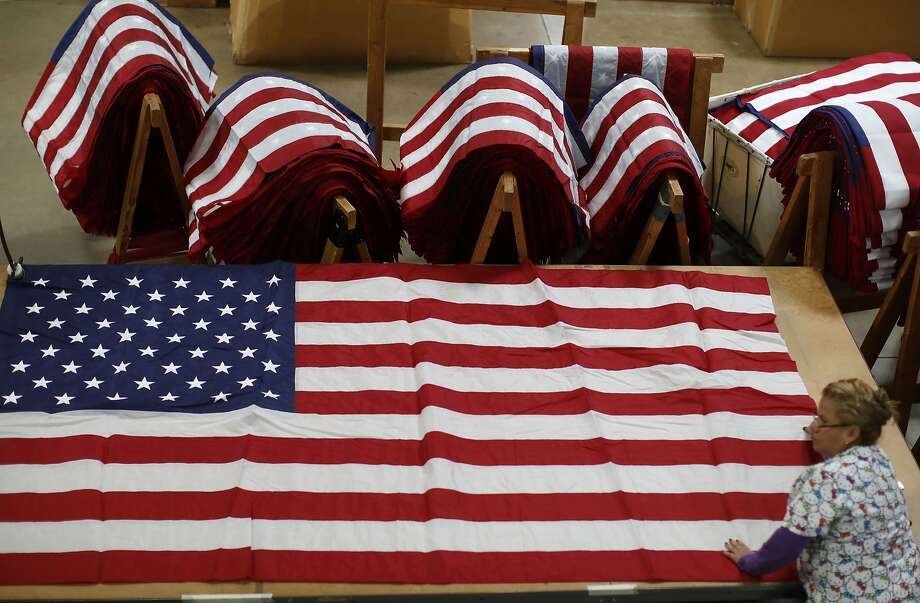 A worker unfurls an American flag at the FlagSource factory in Batavia, Ill. Photo: Jim Young, Bloomberg
