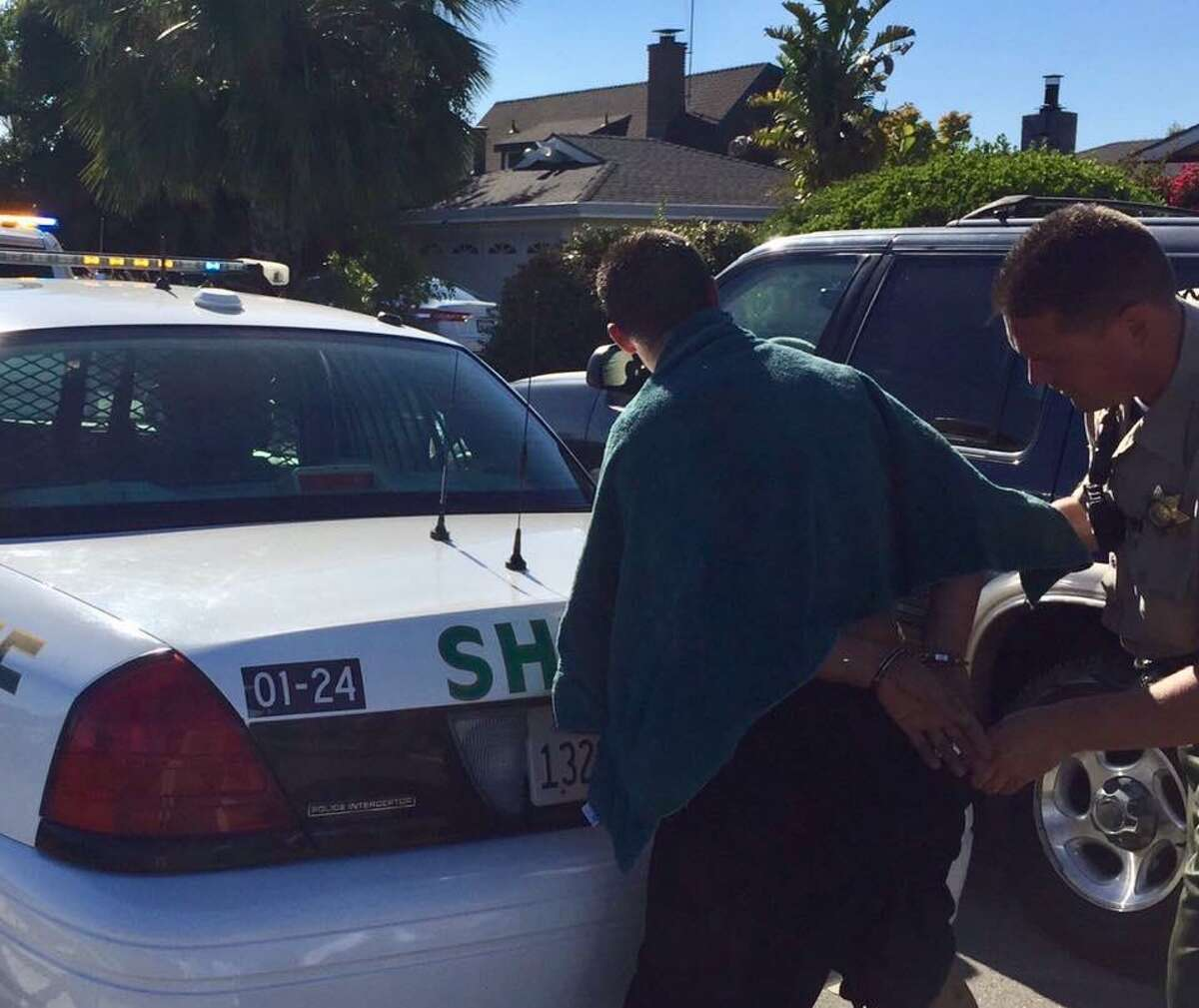 A Marin County Sheriff's deputy takes Francisco Reyes, 34, into custody on a probation violation after he and a pregnant woman were found moving into bank-owned home in Bel Marin Keys. Officials said Reyes answered a scam Craigslist ad and was duped into renting the house.