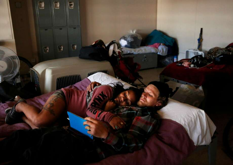 Sami Basu, 23, and her fiance Dustin Johnson, 31, watch a show together on a tablet on their bed in the Navigation Center after a morning of walking around the city to different appointments. Photo: Leah Millis, The Chronicle