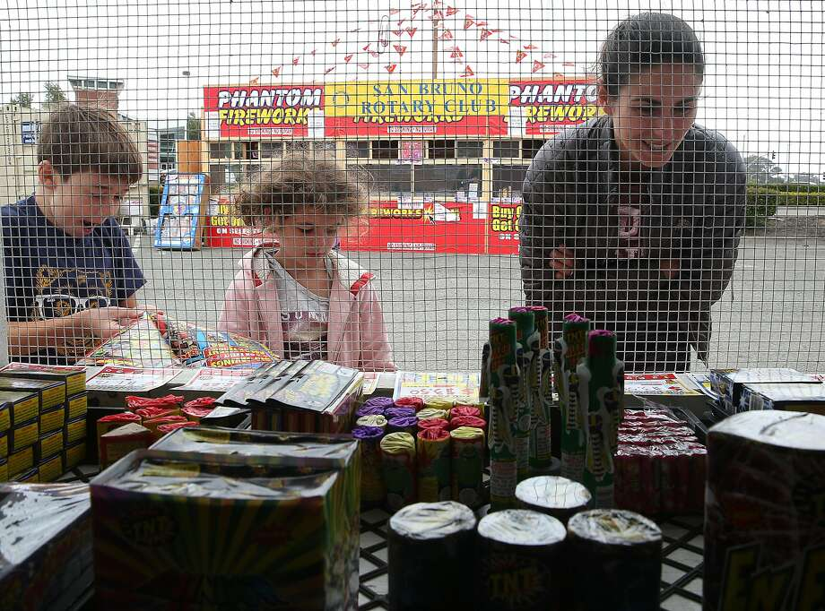 Ten-year-old Anthony Gobliersch (left), and his 8-year-old sister, Cadence Goblirsch, and mother, Hope Gobli ersch, check out fireworks on display in the parking lot of the Shops at Tanforan mall in San Bruno. Photo: Liz Hafalia, The Chronicle