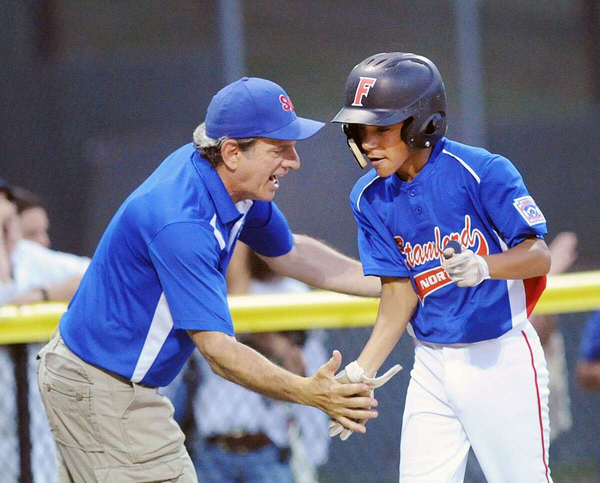 Stamford North manager Craig Ertrachter, left, congratulates his player Antonio Belgrove as Belgrove rounded third base after hitting a three-run home run in the bottom of the second inning of the Little League District 1 baseball game against Weston Friday at the Springdale Little League Field in Stamford.