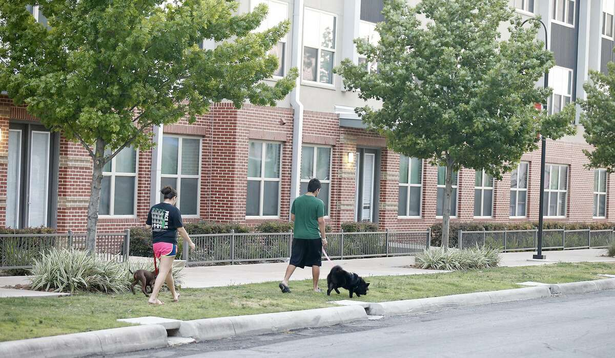 A couple walks their dogs past the area of the officer-involved shooting that occurred Thursday June 29, 2017 near San Antonio College.