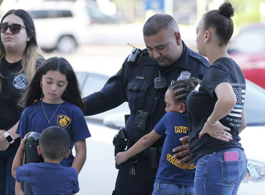 Officer Mario Lozano and his wife Rose Marie along with their children pay respects at a memorial at Public Service Headquarters for fallen San Antonio Police Officer Miguel Moreno on Friday, June 30, 2017. Moreno died a day after suffering a gunshot wound from an assailant near Main and Evergreen Streets on Thursday afternoon. (Kin Man Hui/San Antonio Express-News)