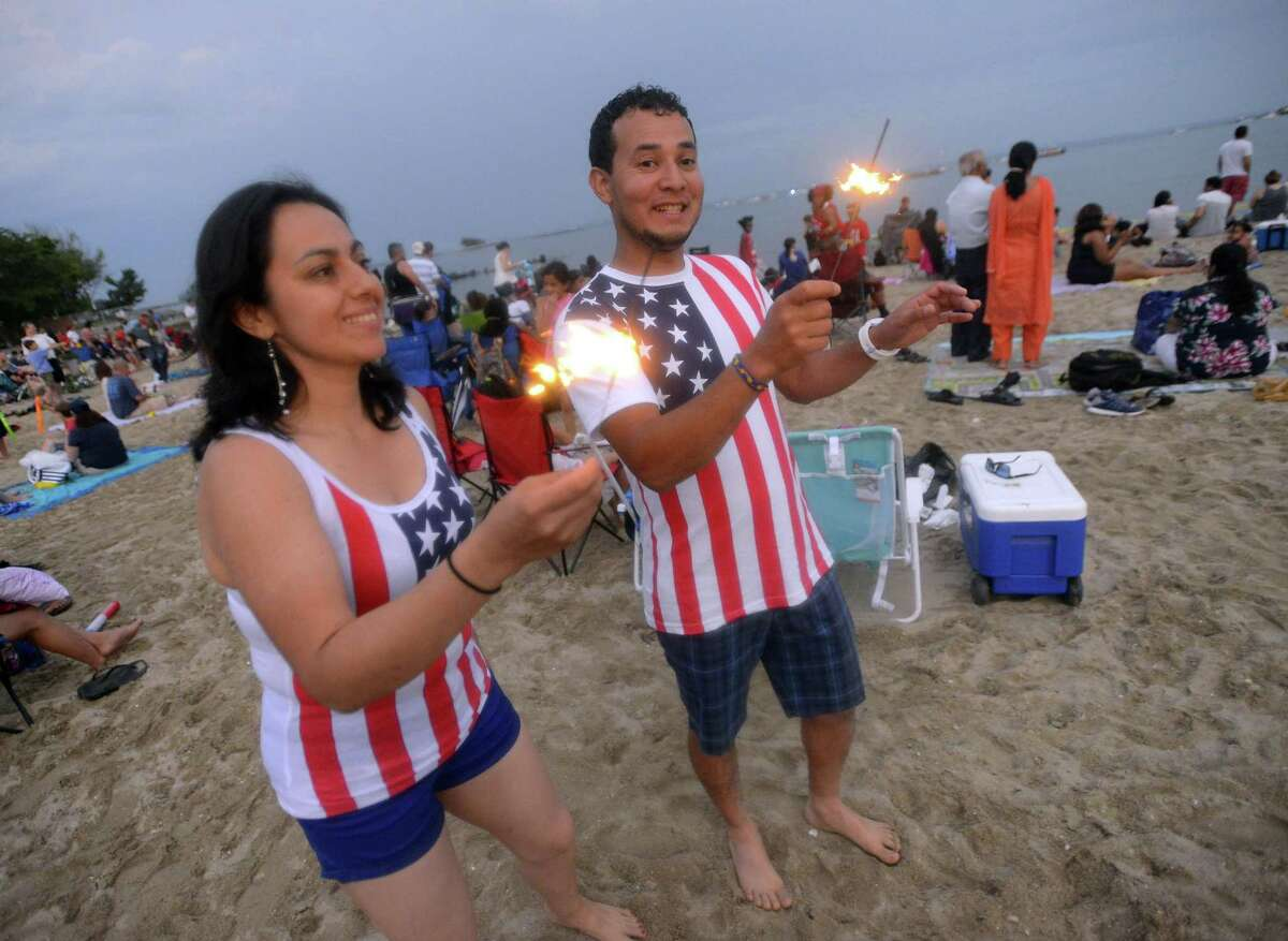 Sondra Ulloa and Oscar Aguero, both of Stamford, dance to music while playing with sparklers prior to a fireworks spectacular lighting up the skies over Cummings Park and Beach on Thursday, June 30, 2017 in Stamford, Connecticut. Several thousand residents weather a passing storm to take in the 20 minute show, enjoying a musical tribute, as they kick off their holiday weekend.
