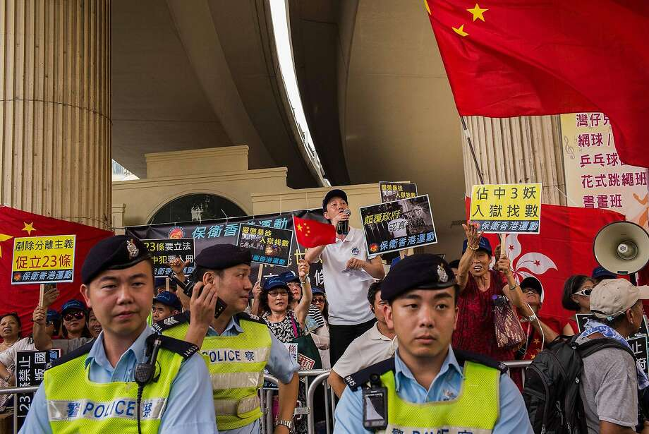 Pro-democracy protesters makes a speech as others wave Chinese national flags behind police officers during a demonstration in Hong Kong on July 1, 2017. (MUST CREDIT: Billy H.C. Kwok/Bloomberg) Photo: Billy H.C. Kwok, Bloomberg