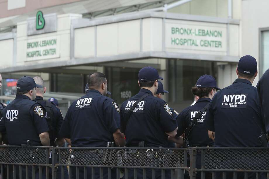 Police officers with the Tactical Response Unit stand guard Friday outside Bronx Lebanon Hospital after a gunman opened fire with an assault rifle and then took his own life. Photo: Mary Altaffer, Associated Press