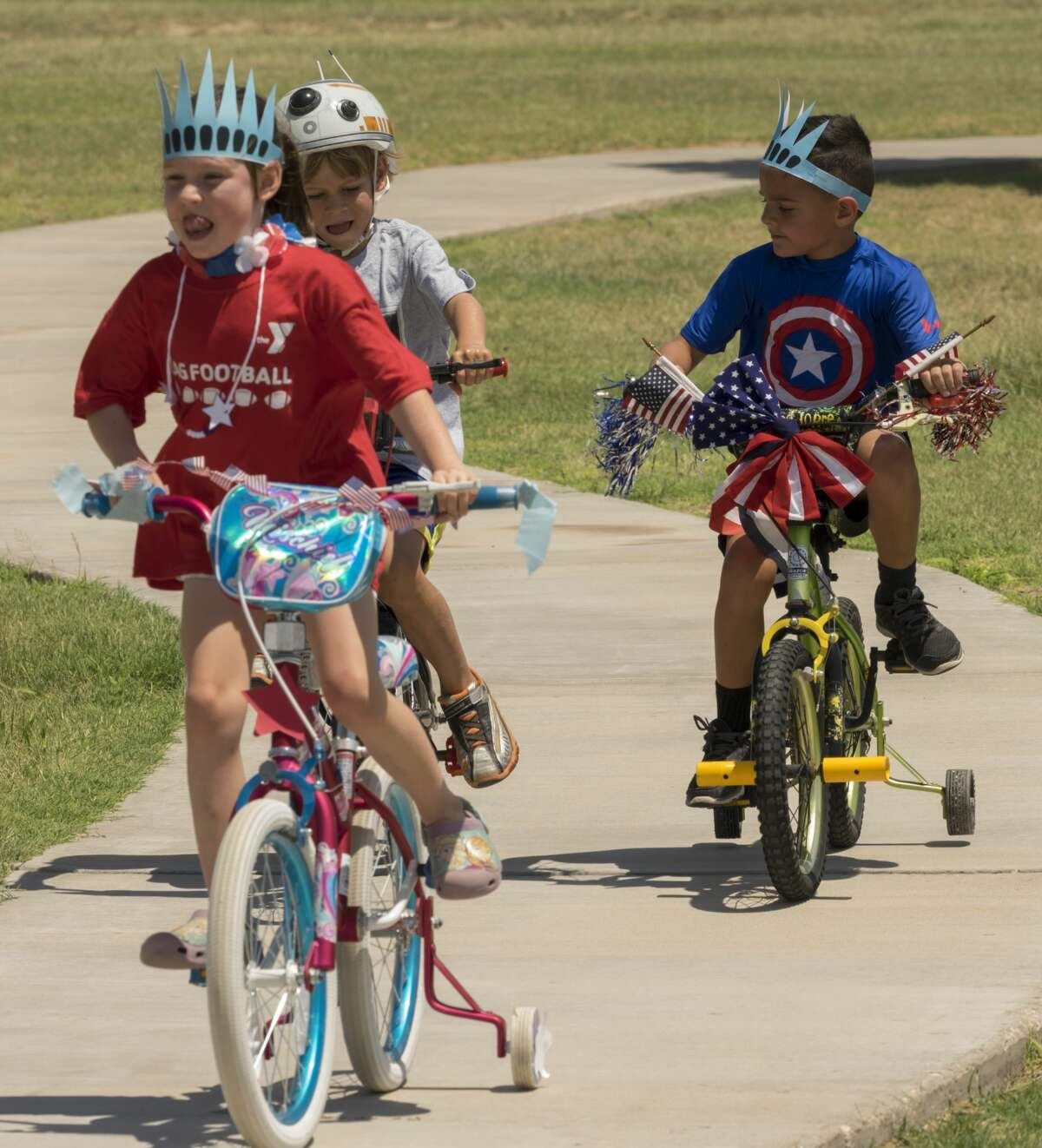 Children ride their decorated bikes in the parade 7/01/17 at the Midland County Library picnic celebrating the 4th of July and the mid-point of the summer reading program. Tim Fischer/Reporter-Telegram