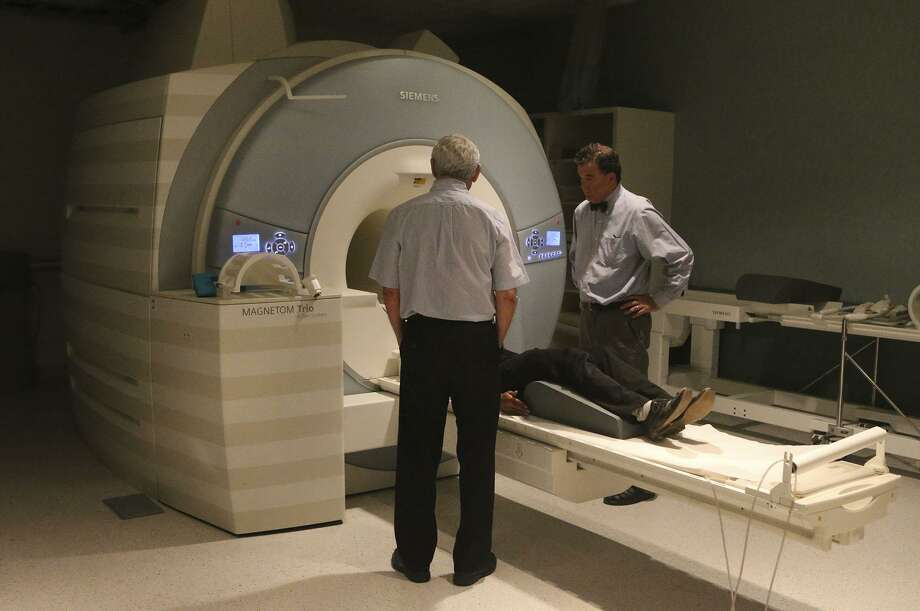 Doctor Peter Fox (right) stands with physicist Jack Lancaster (left) by a magnetic resonance imager at the Univerity of Texas Health Science Center's Greehey Academic and Research Campus. Fox is involved in a study that will test the use of magnetic current to treat depression. Photo: John Davenport, Staff / San Antonio Express-News / ©San Antonio Express-News/John Davenport